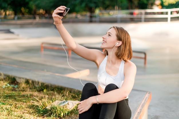 Jugendliche, die selfies nimmt und am telefon im park nach der schule in verbindung steht Premium Fotos