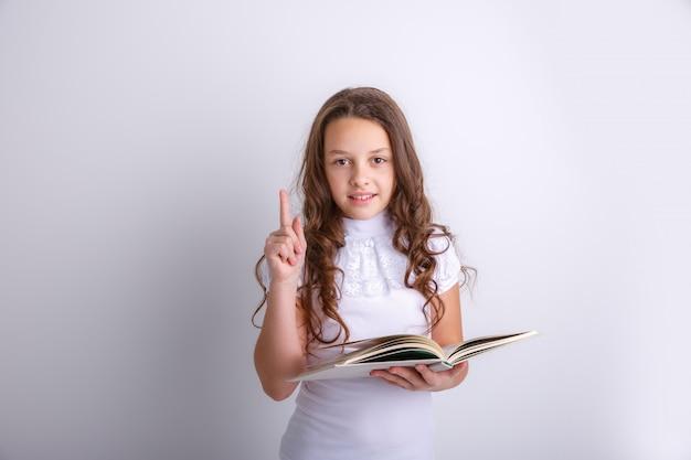 Jugendliche mit einem buch in ihren händen auf einem weißen hintergrund. zeigt emotionen freude, überraschung, trauer. Premium Fotos