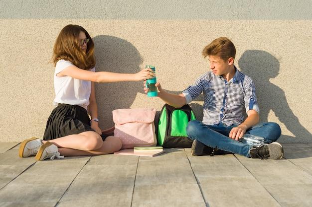 Jugendliche sitzen an der grauen wand Premium Fotos