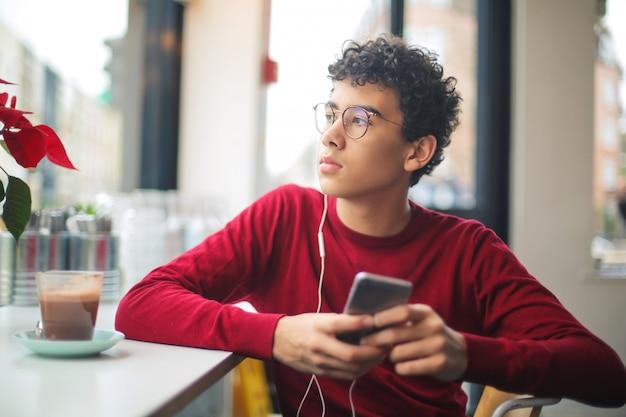 Jugendlicher, der in einer bar sitzt, musik hört und heiße schokolade trinkt Premium Fotos