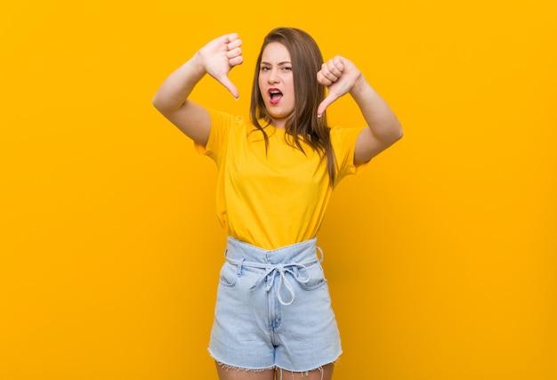Jugendlicher der jungen frau, der ein gelbes hemd unten zeigt daumen und abneigung ausdrückt trägt. Premium Fotos