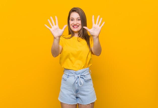 Jugendlicher der jungen frau, der ein gelbes hemd zeigt nr. zehn mit den händen trägt. Premium Fotos