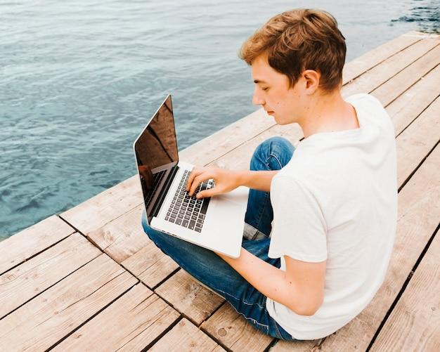 Jugendlicher, der laptop auf dem dock verwendet Kostenlose Fotos
