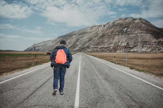 Jugendlicher, der weg auf gebirgsstraße geht. konzept der flucht und abenteuer Premium Fotos