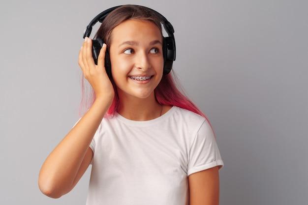 Jugendlicher des jungen mädchens, der musik mit ihren kopfhörern über einem grauen hintergrund hört Premium Fotos