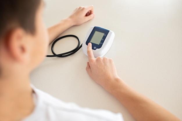 Jugendlicher misst blutdruck mit monitor im haus. Premium Fotos