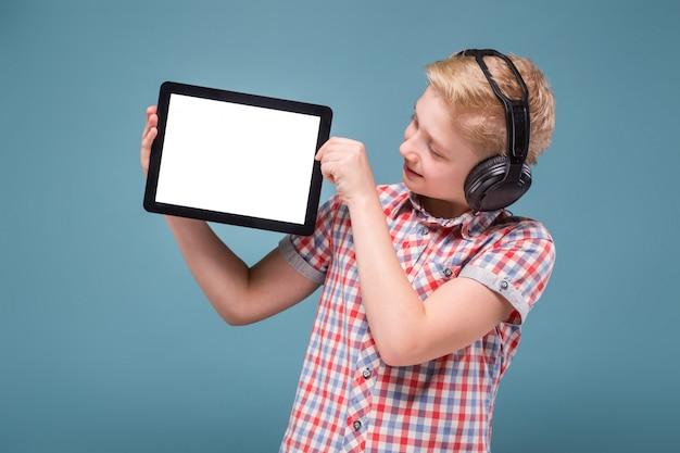Jugendlicher mit kopfhörern zeigt tablettenanzeige, foto mit raum für text Premium Fotos