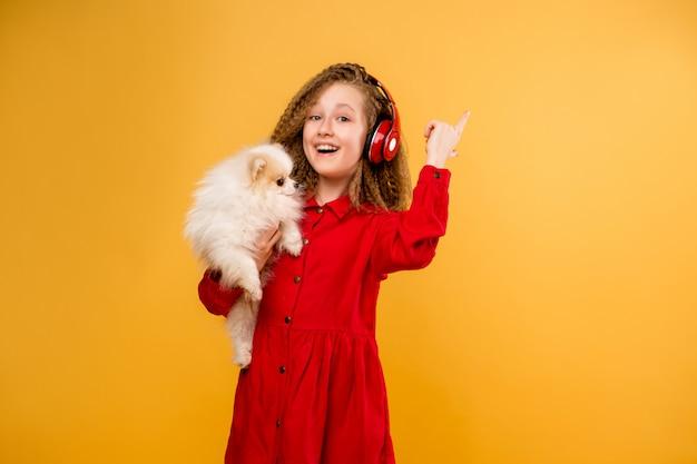 Jugendliches mädchen, das einen kleinen hund in ihren händen hält Premium Fotos