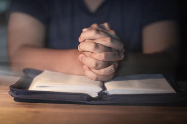 Jugendlichfrauenhand mit dem kreuz und bibel, die, hände beten, faltete sich im gebet Premium Fotos