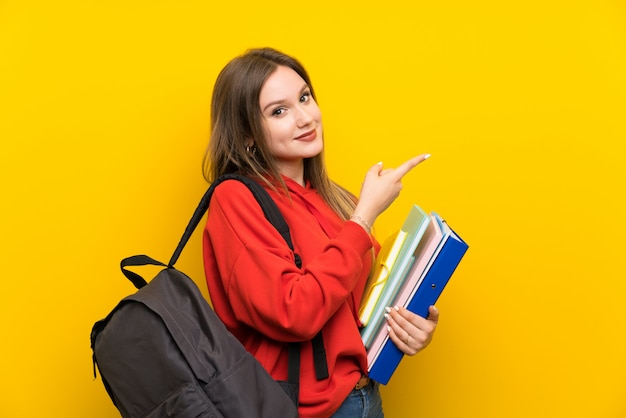 Jugendlichkursteilnehmermädchen über gelbem zeigefinger auf die seite Premium Fotos
