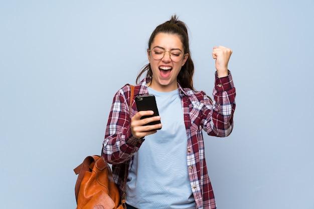 Jugendlichkursteilnehmermädchen über getrennter blauer wand mit telefon in siegstellung Premium Fotos