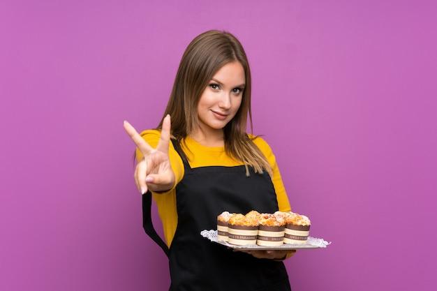Jugendlichmädchen, das viele verschiedene minikuchen über lokalisierter purpurroter wand lächelt und zeigt siegeszeichen hält Premium Fotos