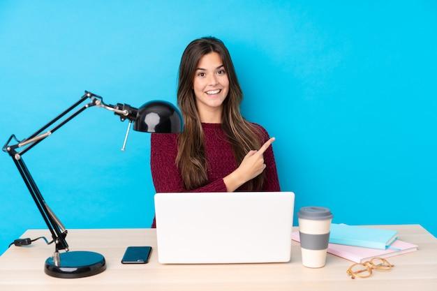 Jugendlichmädchen in einer tabelle mit ihrem pc Premium Fotos