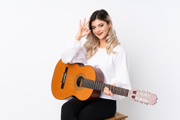 Jugendlichmädchen mit gitarre über dem lokalisierten weiß, das okayzeichen mit den fingern zeigt Premium Fotos