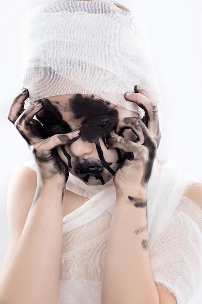 Jugendlichmädchen mit mamaverbänden auf halloween auf weiß lokalisiert Premium Fotos