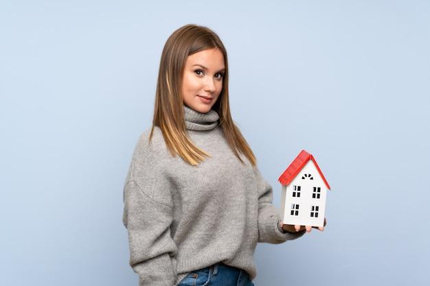 Jugendlichmädchen mit strickjacke über dem lokalisierten blauen hintergrund, der ein kleines haus hält Premium Fotos
