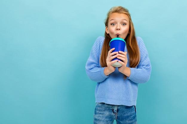 Jugendlichmädchen trinkt glücklich durch einen strohhalm von einem glas auf einem blauen hintergrund Premium Fotos
