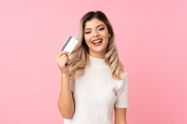 Jugendlichmädchen über dem lokalisierten rosa hintergrund, der eine kreditkarte hält Premium Fotos