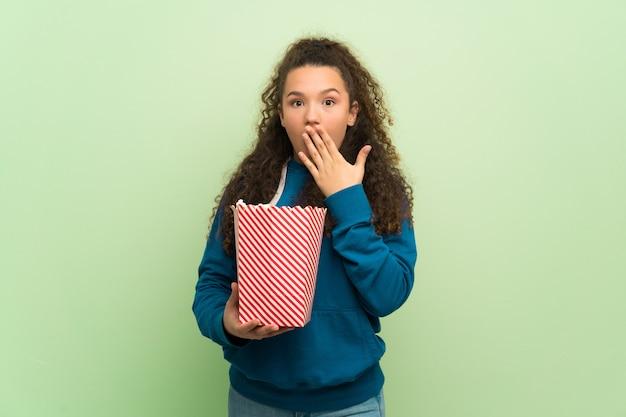 Jugendlichmädchen über der grünen wand überrascht und popcorn essend Premium Fotos