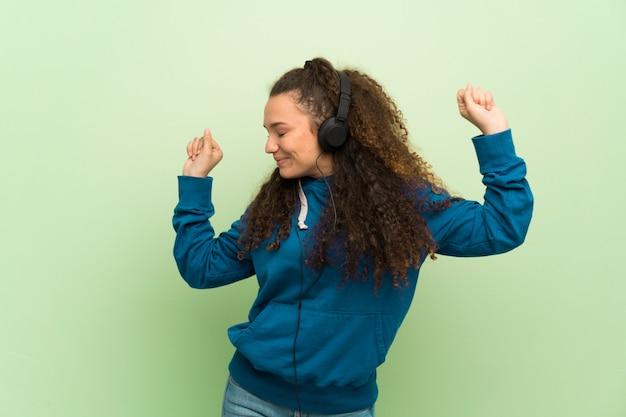 Jugendlichmädchen über grüner wand hörend musik mit kopfhörern und tanzen Premium Fotos