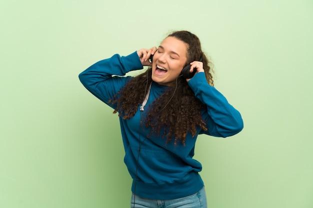 Jugendlichmädchen über grüner wand hörend musik mit kopfhörern Premium Fotos