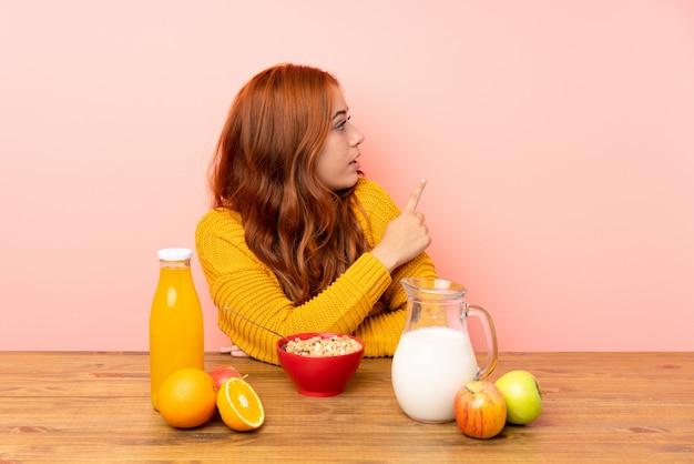 Jugendlichrothaarigemädchen, das in einer tabelle zurück zeigt mit dem zeigefinger frühstückt Premium Fotos