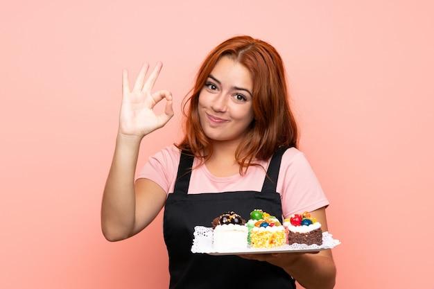 Jugendlichrothaarigemädchen, das viele verschiedene minikuchen über dem lokalisierten rosa zeigt okayzeichen mit den fingern hält Premium Fotos