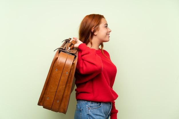 Jugendlichrothaarigemädchen mit strickjacke über dem lokalisierten grün, das einen weinleseaktenkoffer hält Premium Fotos