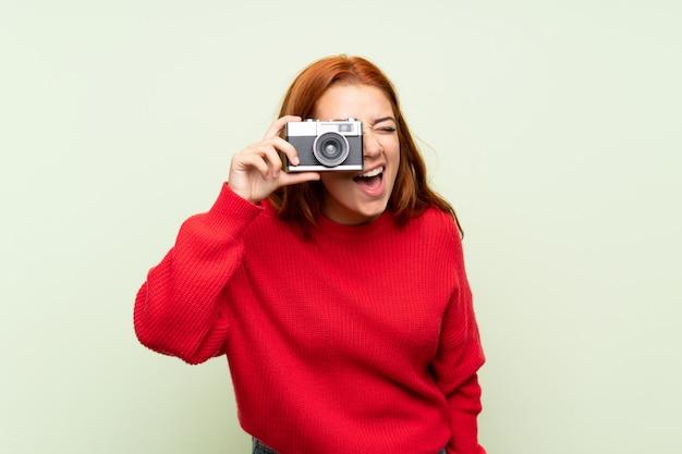 Jugendlichrothaarigemädchen mit strickjacke über der lokalisierten grünen wand, die eine kamera hält Premium Fotos