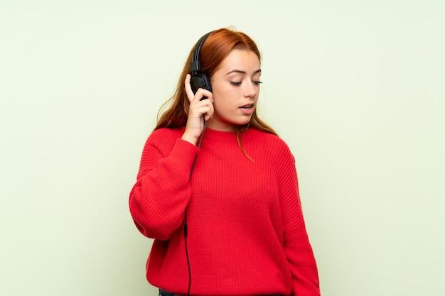 Jugendlichrothaarigemädchen mit strickjacke über lokalisiertem grün hörend musik mit kopfhörern Premium Fotos