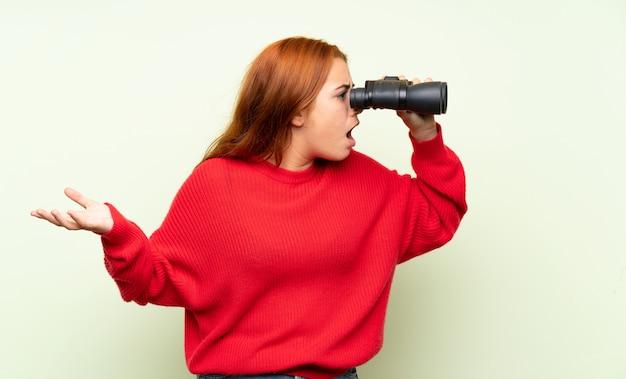 Jugendlichrothaarigemädchen mit strickjacke über lokalisiertem grün mit schwarzen ferngläsern Premium Fotos