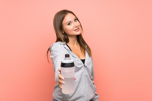 Jugendlichsportmädchen mit einer flasche wasser über lokalisiertem rosa hintergrund Premium Fotos