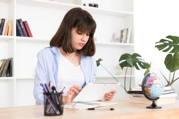 Jugendstudent, der bei tisch sitzt und mit tablette studiert Kostenlose Fotos