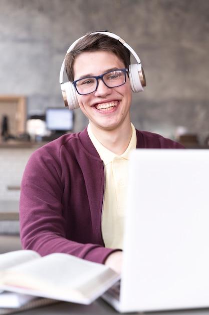 Jugendstudent in den gläsern und in kopfhörern, die bei tisch im klassenzimmer sitzen Kostenlose Fotos