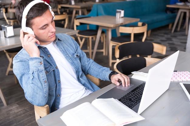 Jugendstudent in den kopfhörern, die bei tisch mit notizbuch sitzen Kostenlose Fotos