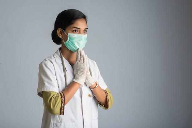 Junge ärztin macht namaste wegen ausbruch von covid-19. neue begrüßung, um die ausbreitung von coronavirus zu vermeiden, anstatt mit einer umarmung oder einem händedruck zu begrüßen. Premium Fotos