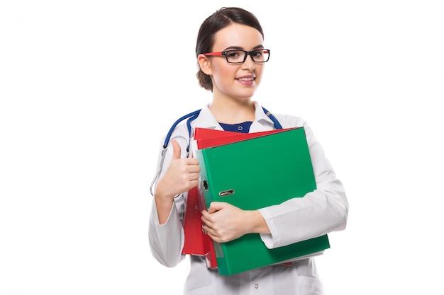 Junge ärztin mit dem stethoskop, das mappen in ihren händen mit dem daumen oben in der weißen uniform auf weiß hält Premium Fotos
