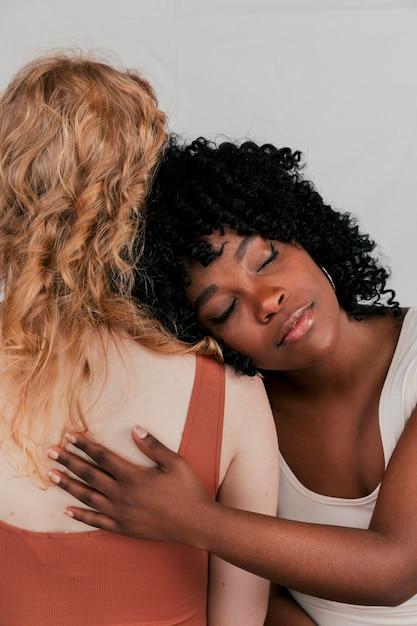 Junge afrikanische frau, die auf der schulter der blonden frau sich lehnt Kostenlose Fotos