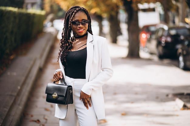 Junge afrikanische frau kleidete im weißen anzug außerhalb der straße an Kostenlose Fotos