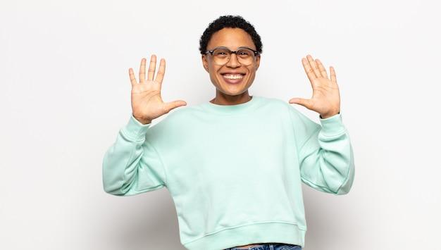Junge afro frau lächelt und sieht freundlich aus, zeigt nummer zehn oder zehntel mit der hand nach vorne und zählt herunter Premium Fotos