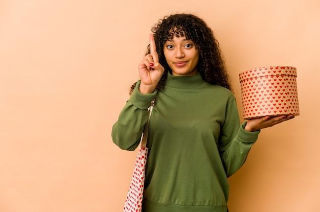 Junge afroamerikaner-afro-frau, die ein valentinstaggeschenk hält, das nummer eins mit finger zeigt. Premium Fotos