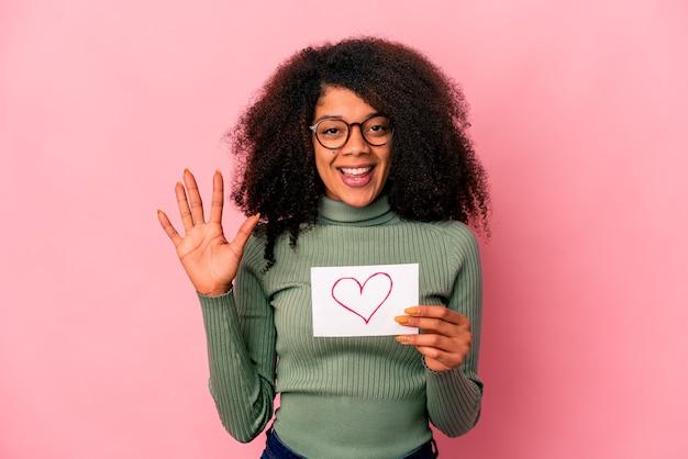 Junge afroamerikaner lockige frau, die ein herzsymbol auf plakat lächelnd fröhlich zeigt nummer fünf mit den fingern hält. Premium Fotos