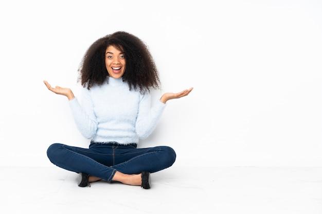 Junge afroamerikanerfrau, die auf dem boden mit schockiertem gesichtsausdruck sitzt Premium Fotos