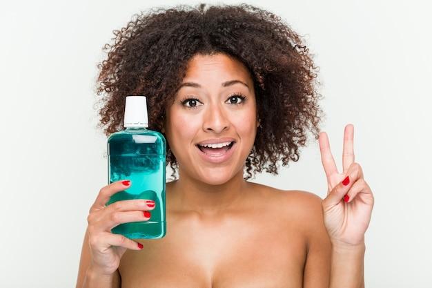 Junge afroamerikanerfrau, die das mundwasser zeigt siegeszeichen und breit lächelt hält. Premium Fotos
