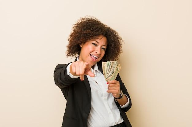 Junge afroamerikanerfrau, die das nette lächeln der dollar zeigt auf front hält. Premium Fotos