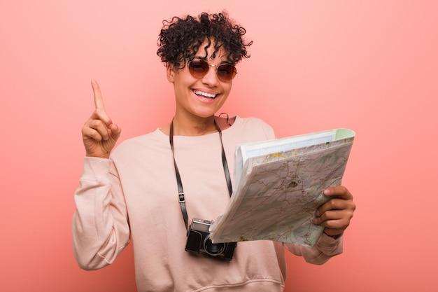 Junge afroamerikanerfrau, die eine karte zeigt nummer eins mit dem finger hält. Premium Fotos
