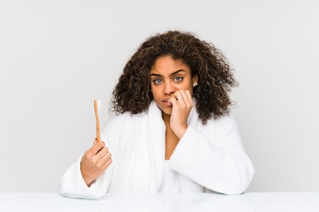 Junge afroamerikanerfrau, die eine zahnbürste hält, die fingernägel beißt, nervös und sehr ängstlich. Premium Fotos