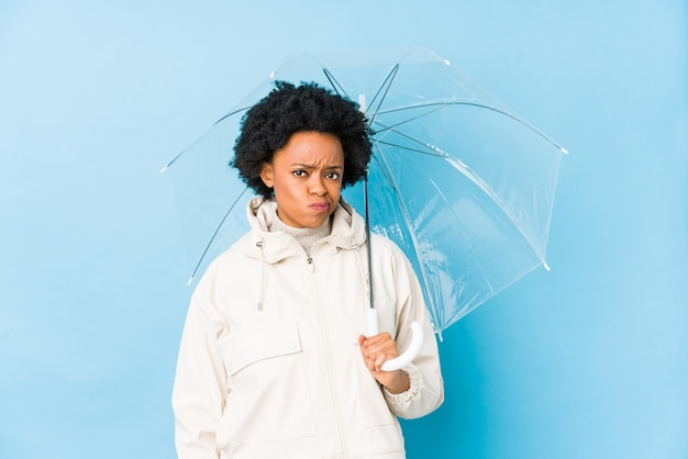 Junge afroamerikanerfrau, die einen regenschirm isoliert hält, verwirrt, fühlt sich zweifelhaft und unsicher. Premium Fotos