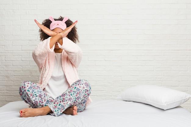 Junge afroamerikanerfrau im tragenden pijama des betts, das zwei arme gekreuzt, ablehnungskonzept hält. Premium Fotos
