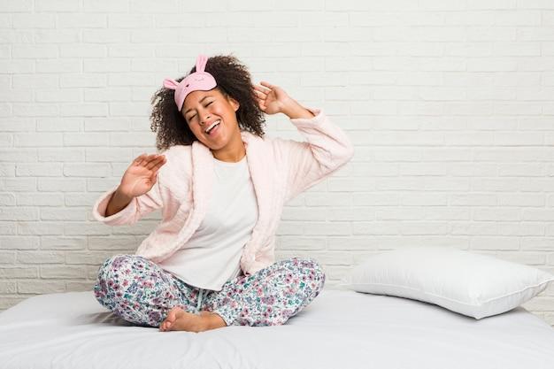 Junge afroamerikanerfrau im tragenden pyjama des betts, der spaß tanzt und hat. Premium Fotos